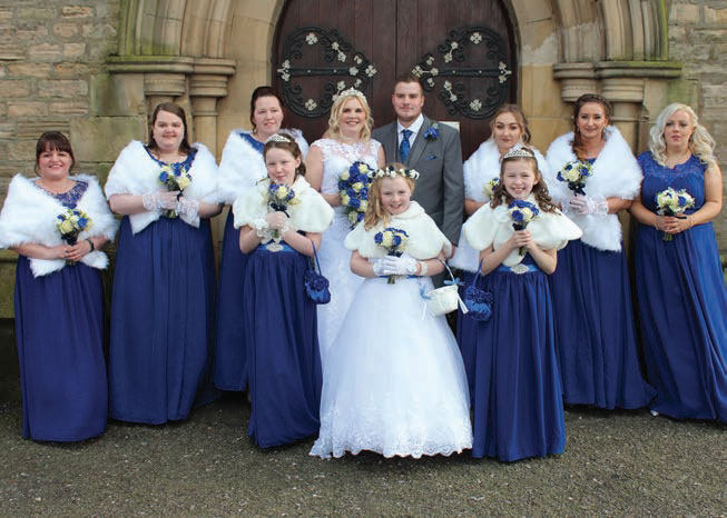 The bridesmaids, flower girls and happy couple gather after the service.