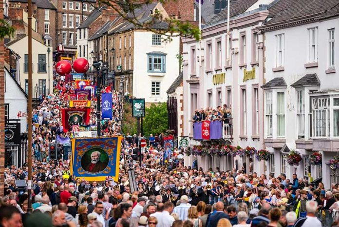 Crowds pass under the balcony of the County Hotel and along Old Elvet at the 2019 Durham Miners' Gala.