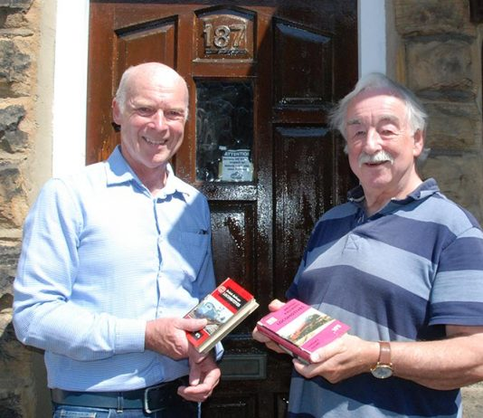 Kevin Shaw and Michael Hall with the books returned books after years.
